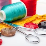 Sewing supplies including thread, button, tape measure, and pins over white background, selective focus
